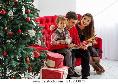 Happy Family Reads A Book Near A Christmas Tree