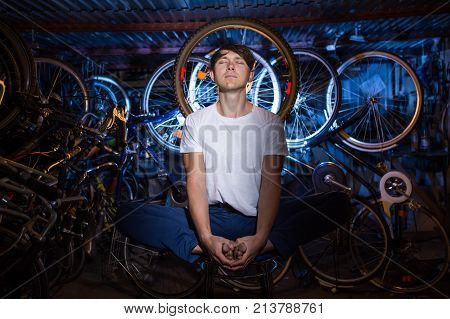 Young Man Is Practicing Yoga In Garage With Many Bicycles Behind Him