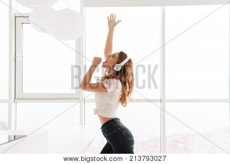 Photo of emotional young lady listening music with headphones dancing and singing near window.