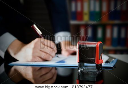 Businessman Working With Document. Automatic Stamp In Foreground