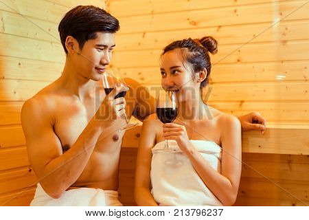 Couple at sauna spa healthy concept Young asian man and woman together sitting in room with hot warm steam happy relaxing resting for health care and skin in holiday with drinking cocktail wine