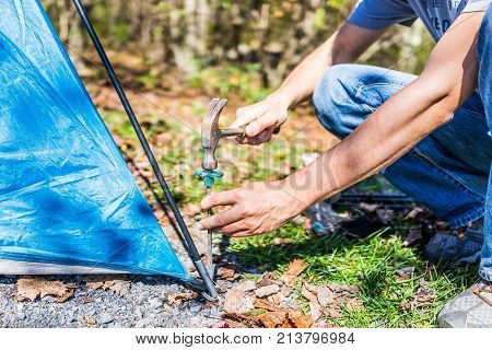 Young Man Setting Up Camp Tent For Camping Trip On Campground By Hammering Nail To The Ground With H