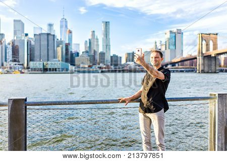 Young Hipster Man Standing Taking Selfie Picture By Fence In Brooklyn Bridge Park Overlooking The Ny
