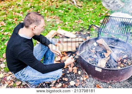 Closeup Of Young Man Roasting One White Marshmallow Caramelizing On Fire Showing Detail And Texture