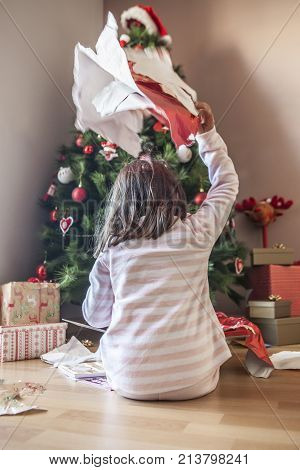 Little girl opening her gifts under Christmas tree early in the morning. She is illuminated by morning natural light