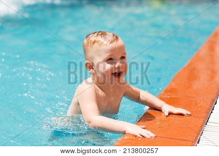cbfa991833 Portrait of happy little Caucasian boy swimming in outdoor pool and  smiling. Summer vacation,