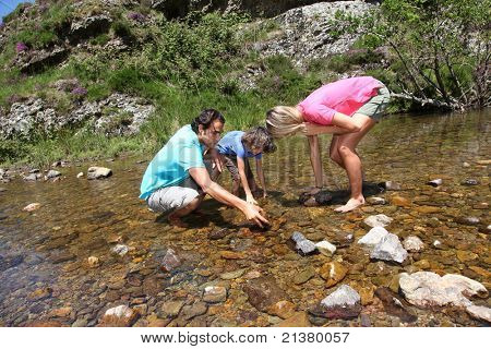 Family playing in river with peebles
