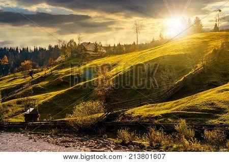 grassy rural hillside near the village at sunset. beautiful countryside scenery in autumn