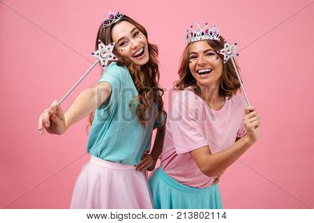 Portrait of happy excited girls dressed in princess costumes holding magical wands and looking camera isolated over pink background