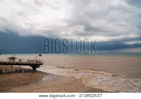 Heavy storm clouds approaching the beach, brown runoff water from a river turning the ocean bown