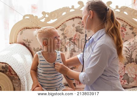 Portrait of young Caucasian female doctor sitting on sofa and listening heartbeat of smiling little boy indoor. Pediatrics and health concept