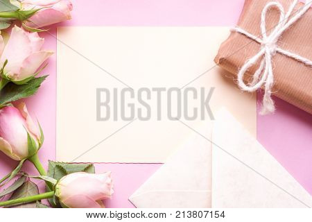 Message card with flowers and gift - Gifting theme image with a blank paper in the middle surrounded by lovely pink roses an envelope and a gift box wrapped in brown paper on a pink background.