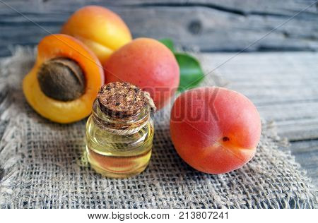 The apricot kernel oi in a glass jar and fresh ripe apricots on old wooden background. Essential apricot oil for spa,beauty treatment, aromatherapy and bodycare.Selective focus.
