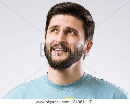 Portrait of bearded dreamer thinking on grey background