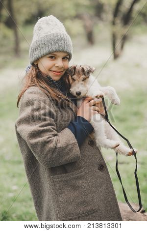 Girl playing with a dog fox terrier. Outdoor