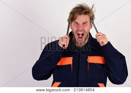 Man With Screaming Face Holds Wrench Tools Near Face