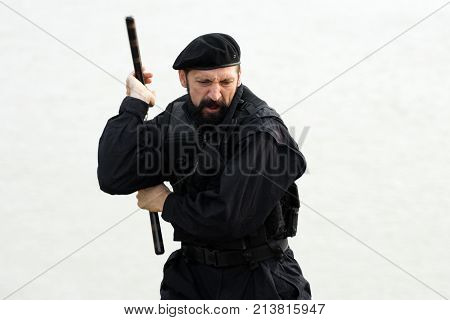 The security man in uniform and beret is practicing with nunchaku on white background.