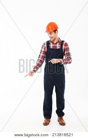 Full length portrait of a smiling young male builder pointing two fingers down while standing isolated over white background