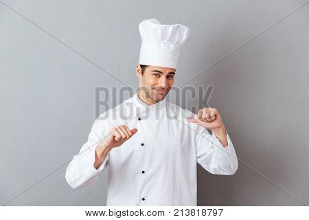Image of cheerful young cook in uniform standing isolated over grey wall background. Looking camera pointing to himself.