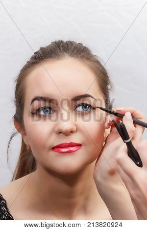 Make-up artist make eye make-up arrows on eyes close-up