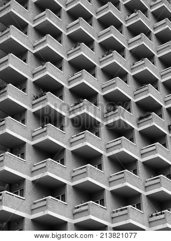 large highrise modern apartment building with large number of repeating geometric balconies in monochrome poster