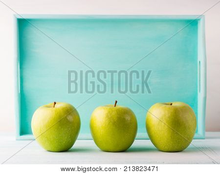 Three Green apples on turquoise background. Healthy food three pillars concept.
