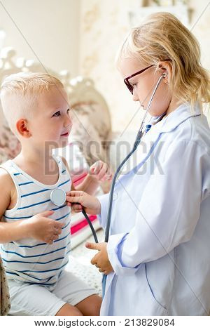 Portrait of serious little girl wearing glasses and lab coat listening heartbeat of her brother while playing doctor at home. Occupation, health and childhood concept