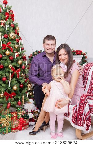 Christmas or New year celebration. Happy young family sitting in chair near Christmas tree with xmas gifts. A fireplace with christmas stocking on background