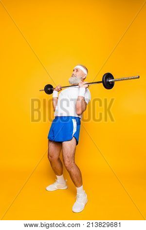 Full Length Of Confident Cool Grandpa With Serious Grimace Exercising Holding Equipment, Lifts It Up