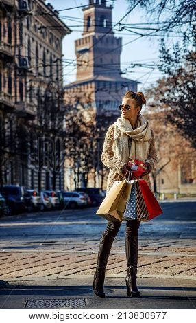 Rediscovering things everybody love in Milan. Full length portrait of elegant traveller woman with shopping bags and Christmas gift near Sforza Castle in Milan Italy looking into the distance