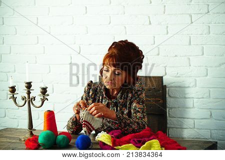 Needlework and knitting hobby. Granny character at Christmas eve. Old lady or grandmother with needle and yarn. Old woman knitting socks from colorful thread. Pension and retirement old age.