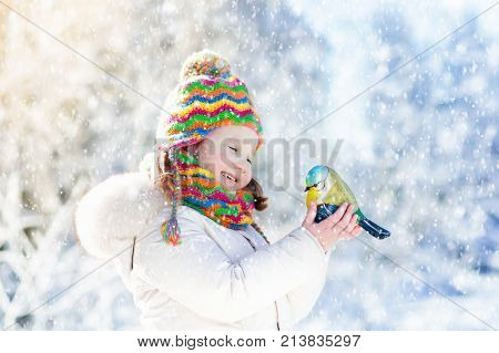 Child Feeding Bird In Winter Park. Kids Play In Snow. Nature And Animals.
