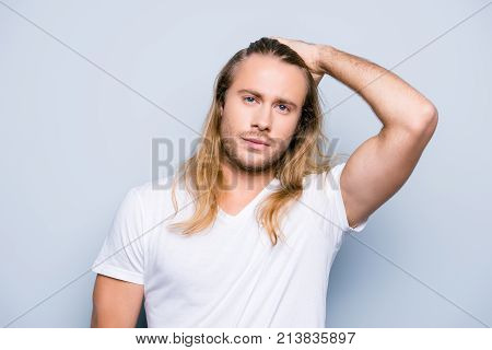 Handsome Brutal Man With Bristle Is Combing His Long Blonde Hair Using His Hand Recently  He Has Vis