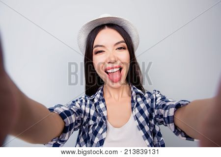 Pretty Charming Girl In Casual Clothes And Hat Is Taking A Self Portarit And Showing Tongue. She Is