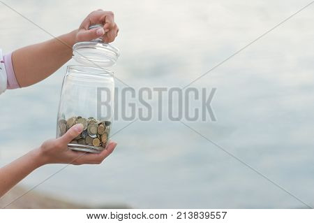 Investment, retirement, taxes and passive income concept. Coins in a glass jar in hand, blur focus