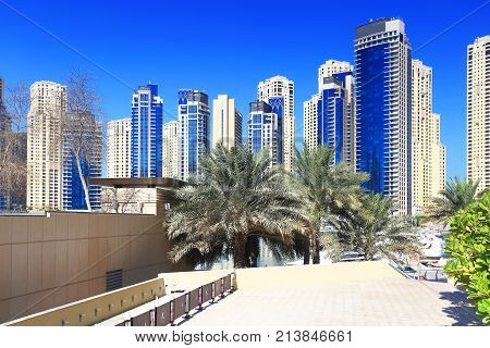 Luxury residential district with palms on blue sky background. Skyscrapers in marina bay district in Dubai.