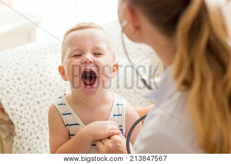 Portrait of funny little Caucasian boy opening mouth for female doctor during medical checkup. Pediatrics and health concept