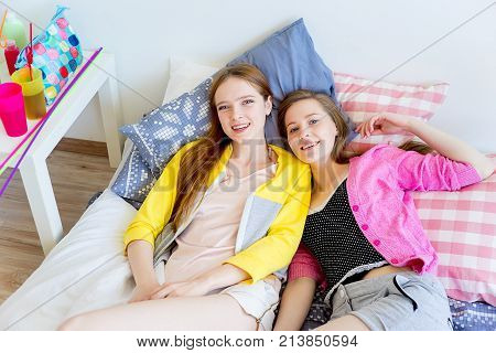 A portrait of two girls telling gossip at a sleepover