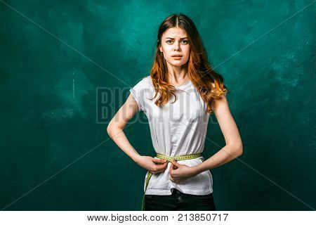 sad young girl in a white T-shirt measures the waist