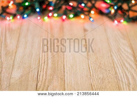 Blank wooden board and colored lights, selective focus, room for copy
