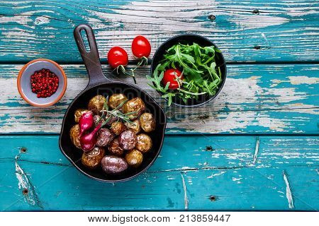 Flat-lay of rural dinner table with fried baby potatoes in old cast iron pan and salad with tomato and arugula in bowl on turquoise vintage background. Healthy food concept. Top view copy space