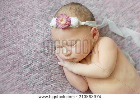 Cute newborn baby girl is sleeping on her side wearing flower headband. Close-up shot.