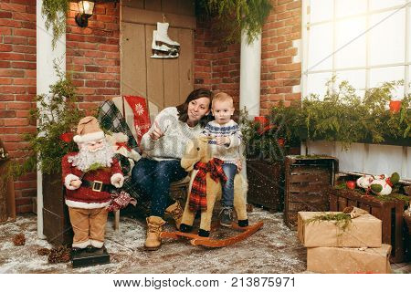 Young Happy Mother With A Cute Little Child Boy On Rocking Horse, Dressed In Sweater In Decorated Ne