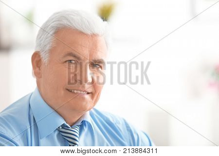 Handsome mature man in formal clothes at home