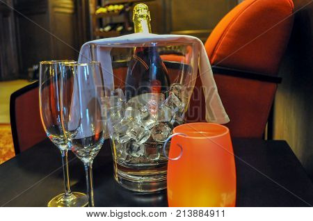 Sparkling wine in ice bucket and two glasses of champagne