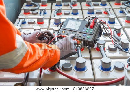 Electrician specialist inspect check voltage and internal resistance of batteries by using battery to preventive maintenance offshore oil and gas occupational.