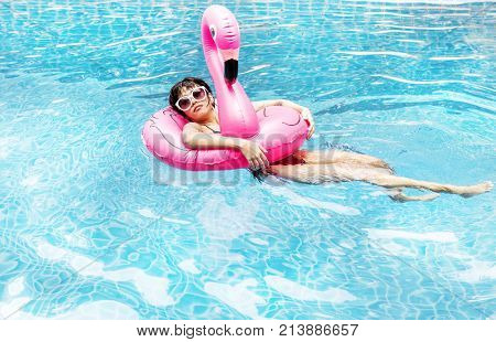 An Asian woman floating in the pool with inflatable floats
