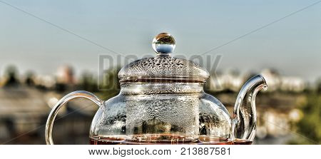 Tea. Teapot With Tea. Breakfast. Tea In A Glass Teapot On The Background Of The Modern City. Summer