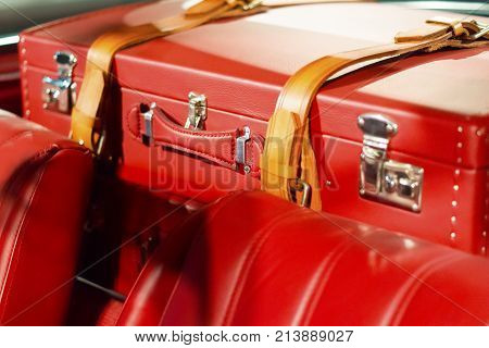 Leather travel suitcase fixed in the car and ready to travel. Active leisure concept.Vintage style