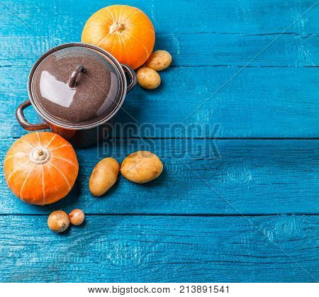 Photo of pot with lid, potatoes, pumpkins, onions on blue wooden table, empty space for text